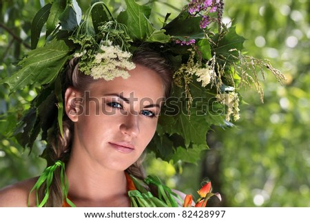 Portrait of a young girl with the diadem of flowers and leaves on his head on a green background, dressed up for the holiday of Ivan Kupala (John Baptist's Day) #82428997