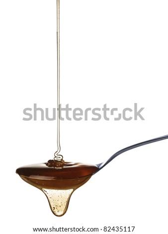 The honey slowly falls onto the spoon. #82435117
