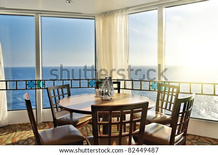interior of a dinner lounge on a cruise ship - with a round table and windows with panorama seaview #82449487