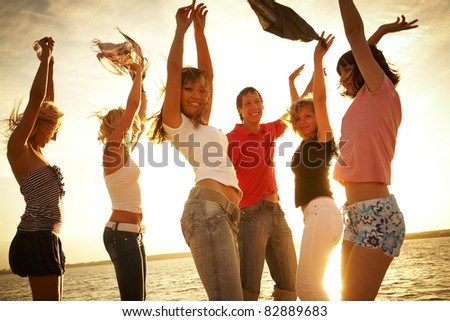 group of happy young people dancing at the beach on  beautiful summer sunset #82889683