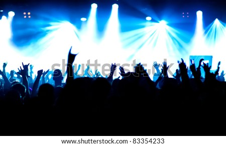 silhouettes of concert crowd in front of bright stage lights #83354233