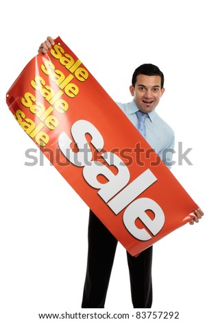 A happy excited businessman, salesman or storeperson holding a vinyl sale banner sign ready to hang.