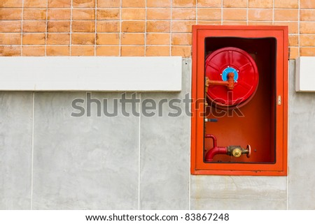 Hydrant with water hoses and fire extinguish equipment on wall #83867248