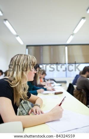 young pretty female college student sitting in a classroom full of students during class (shallow DOF; color toned image) #84324559