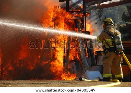 ROSEBURG, OR - SEPTEMBER 03: Single fire fighter sprays a straight steam into a fully involved shop fire off of Breezy Lane, September 03, 2011 in Roseburg, OR #84385549