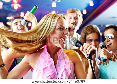 Portrait of joyous girl singing at party on background of happy friends #84460789