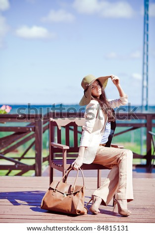 Photo of a young beautiful woman brunette fashion fabrics in today's casual elegant hat with a bag #84815131