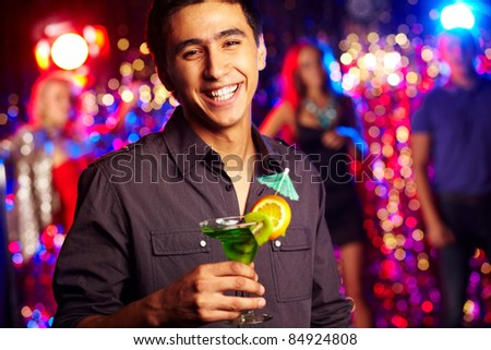 Image of happy guy holding cocktail at party