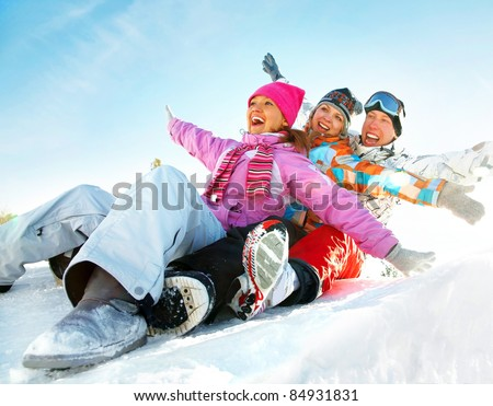 Group of  teenagers slide downhill in wintertime
