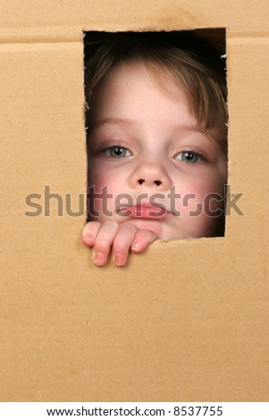 young girl looking from brown carton box #8537755