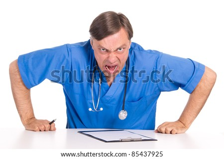 cute doctor in blue posing at table #85437925