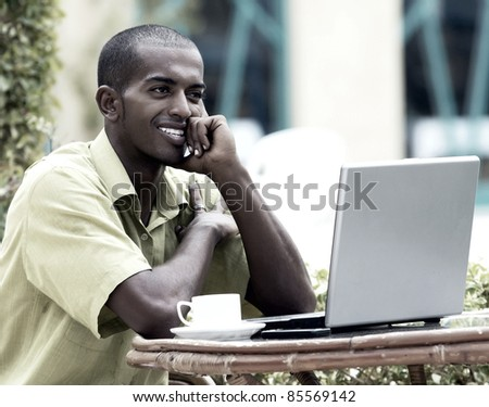 Young happy man or student with laptop sitting at the table #85569142