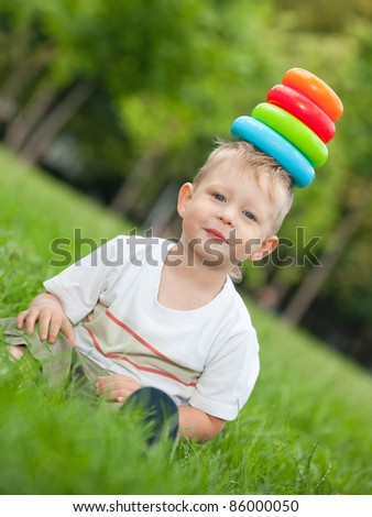 A cheerful boy is holding toy pyramid on his head #86000050