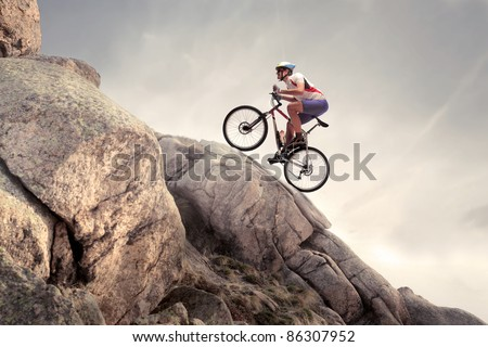 Cyclist climbing on a rock Royalty-Free Stock Photo #86307952