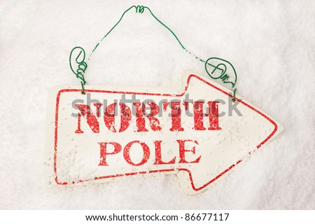 A white sign showing the way to the north pole sat in snow