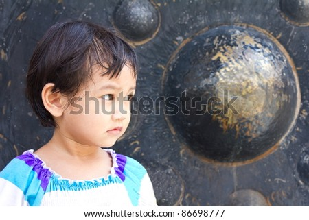 Thai children is located near a large black gong  looking at something. #86698777