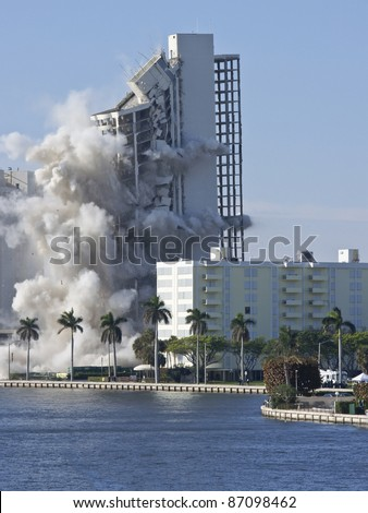 apartment building demolition using blast of dynamite Royalty-Free Stock Photo #87098462