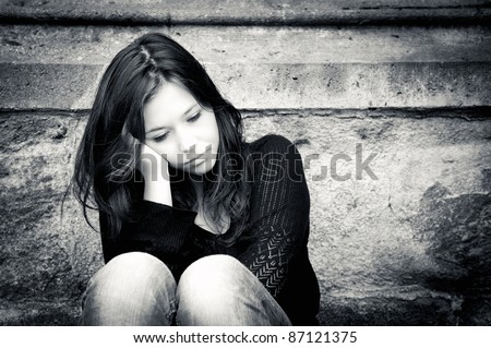Outdoor portrait of a sad teenage girl looking thoughtful about troubles, toned black and white photo Royalty-Free Stock Photo #87121375