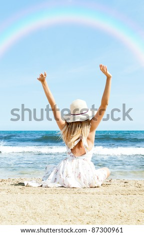 Portrait of young woman on the beach near the sea sitting with hands up wearing sophistical dress and hat looking at rainbow. Photo from behind