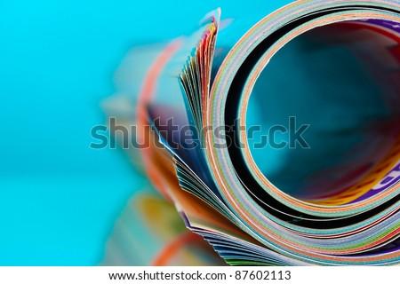 Rolled up magazines on blue background Royalty-Free Stock Photo #87602113