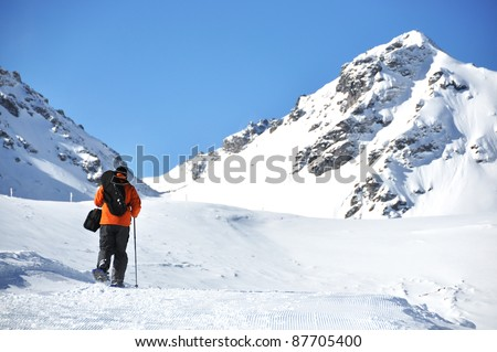 A man hiking in snowshoes along the mountain track #87705400