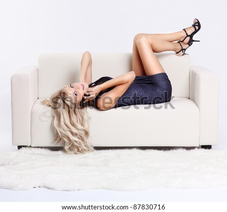 full-length portrait of beautiful young blond woman on couch speaking over her mobile phone #87830716