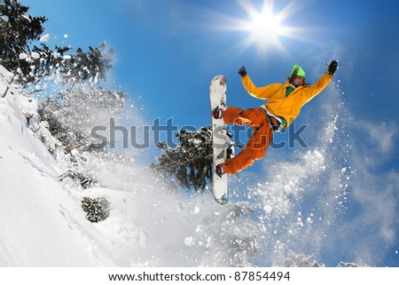Snowboarder jumping against blue sky #87854494