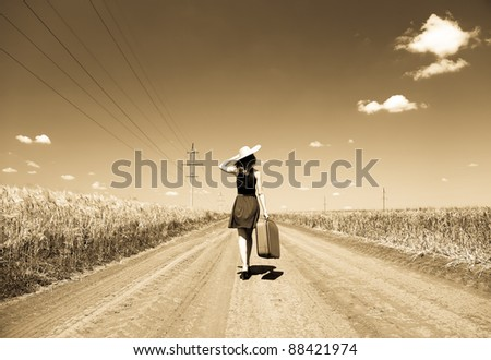 Lonely girl with suitcase at country road. Photo in old yellow color image style. #88421974