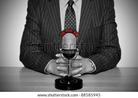 Photo of a news broadcaster sat at a desk and retro microphone with an On The Air illuminated sign, converted to B&W retaining the colour of the text and added vignette for a vintage look.
