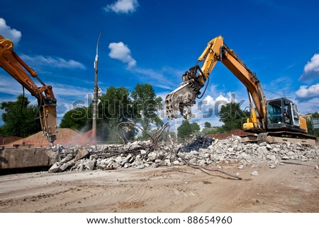 Site Demolition with Crushing Equipments Machines during Breaking Reinforced Concrete Structures Royalty-Free Stock Photo #88654960