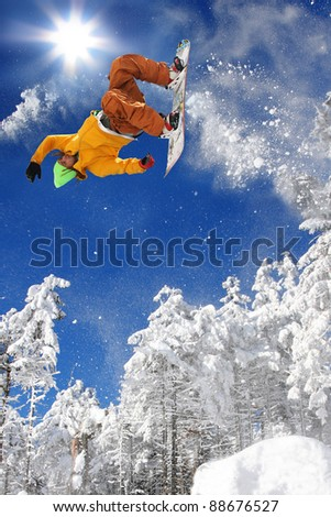 Snowboarder jumping against blue sky #88676527
