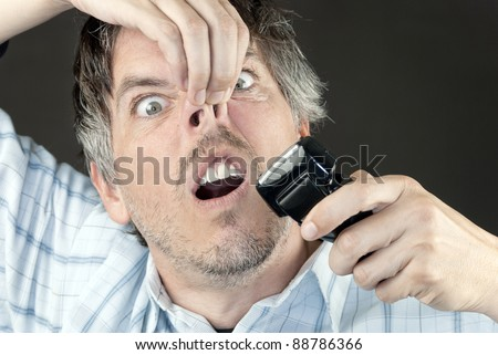 Cloe-up of a man attempting to trim his nose hair with a full sized electric razor. #88786366