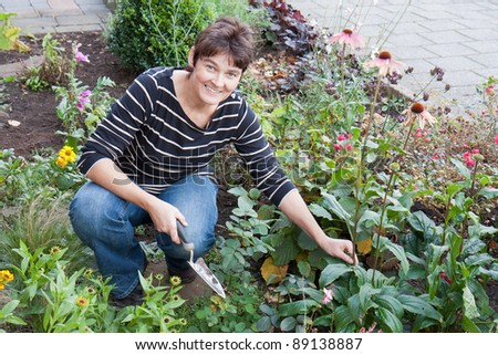 A woman is gardening in the front garden of her house #89138887