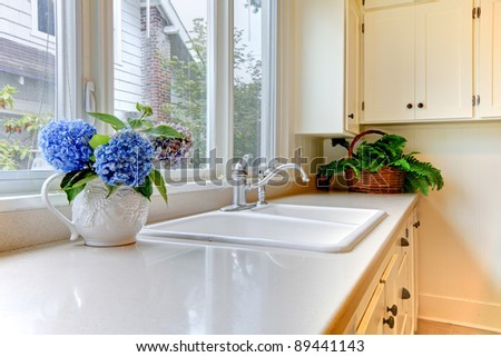 Beautiful kitchen with flowers and white cabinets.