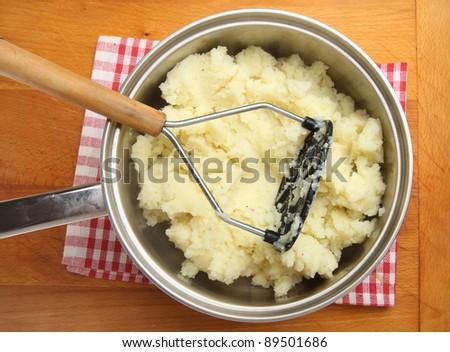 Seasoned potatoes being mashed in stainless steel saucepan. #89501686