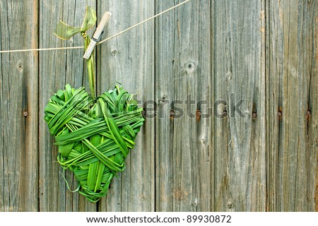 heart of green grass hanging against weathered old wooden wall #89930872