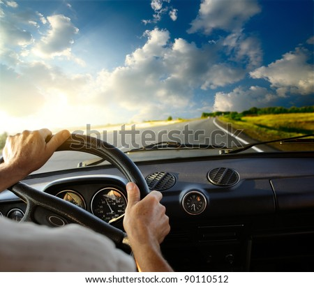 Hands of a driver on steering wheel of a car and empty asphalt road #90110512