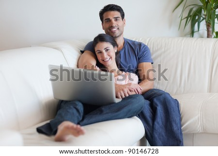 Couple watching a movie with a laptop in their living room #90146728