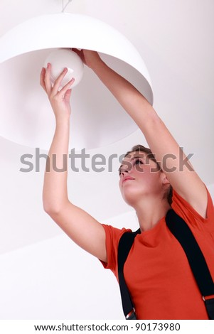 Woman fixing ceiling light #90173980