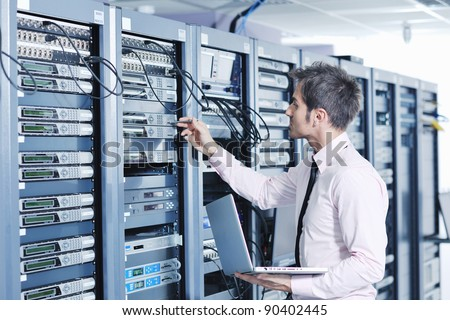 young engeneer business man with thin modern aluminium laptop in network server room Royalty-Free Stock Photo #90402445