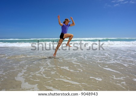 Man leaps while running on sea beach under dramatic skies. Shot in Hermanus, Walker Bay, Western Cape, South Africa. #9048943