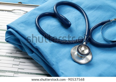A stethoscope shaping a heart and a clipboard on a medical uniform, closeup Royalty-Free Stock Photo #90537568