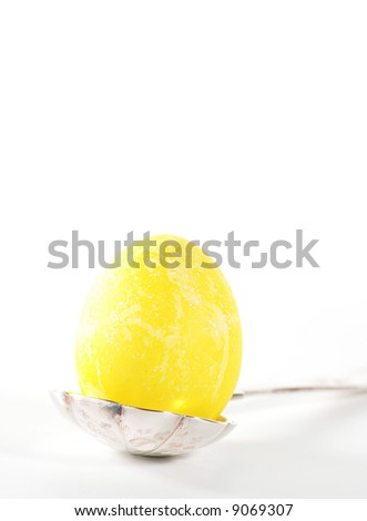 bright yellow Easter egg sitting in a sterling silver spoon #9069307