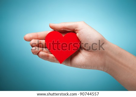 woman's hand holding symbol - red heart. Against blue background #90744557