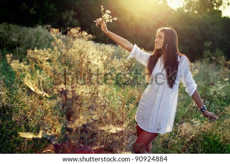 Happy brunette girl relaxing in the field at sunset #90924884