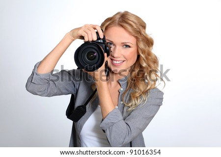 Woman using photo camera in studio