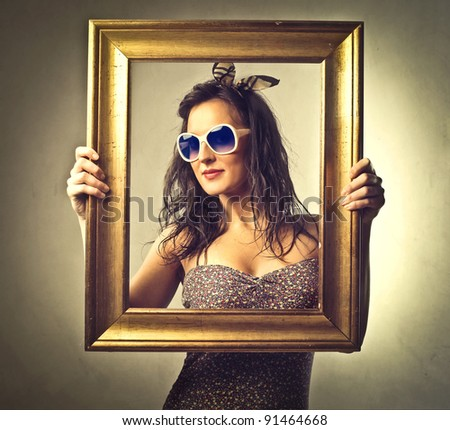 Beautiful woman holding an empty frame