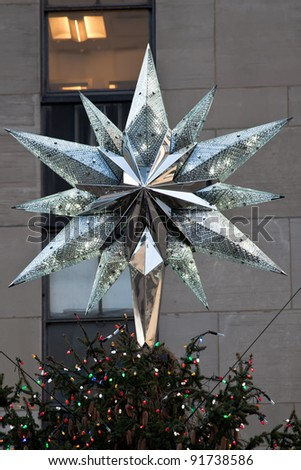 NEW YORK - DEC 30 : The 2011 Swarovski Star on top of the Rockefeller Christmas tree on December 30, 2011 in New York, NY.  The 2011 Swarovski Star's 12 rays are outfitted with 720 LED bulbs. #91738586