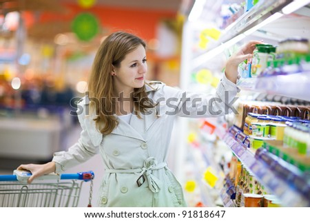 Beautiful young woman shopping for fruits and vegetables in produce department of a grocery store/supermarket (color toned image) #91818647