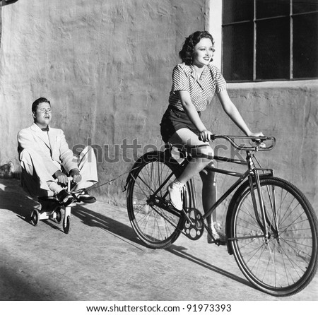 Woman on a bicycle pulling a grown man on a toy tricycle #91973393